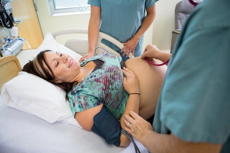 Midsection of nurses examining smiling pregnant woman in hospital room Stock Photo - 25778284