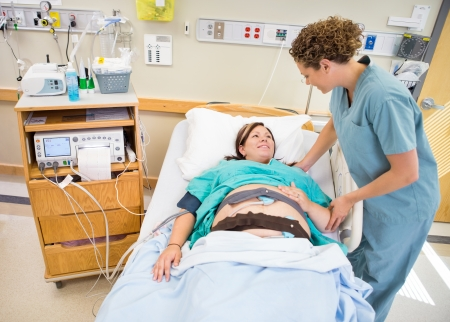 labor: Mid adult female nurse communicating with pregnant patient lying in hospital bed Stock Photo