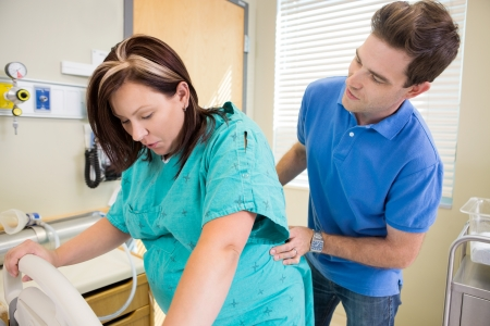 giving back: Mid adult man looking at pregnant wife while massaging lower back