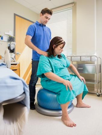 妊娠中の女性の夫は病院の部屋で彼女の肩をメッセージ間運動ボールの上に座って
