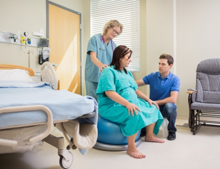 midwife: Mature nurse and man assisting pregnant woman on exercise ball in hospital Stock Photo
