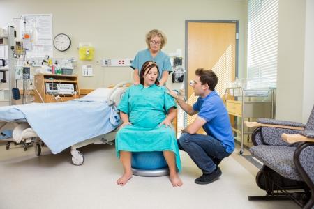 Volwassen verpleegkundige en man troosten zwangere vrouw ondergaat een samentrekking zittend op de uitoefening bal in het ziekenhuis