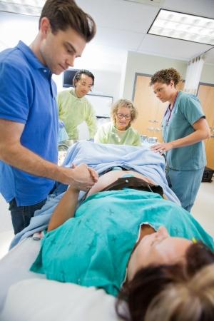 sala parto: Met� uomo adulto tiene la mano della donna durante il parto in ospedale camera Archivio Fotografico