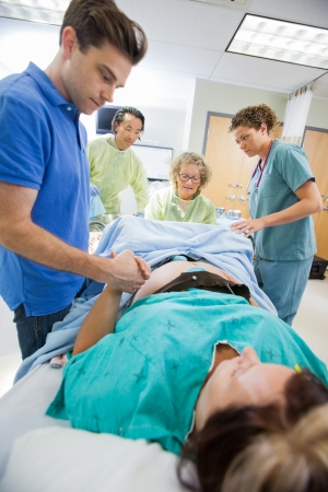 delivery room: Mid adult man holding womans hand during delivery in hospital room Stock Photo