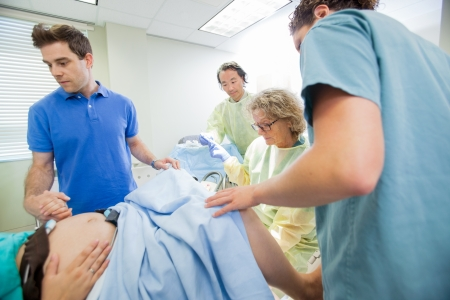delivery room: Medical team examining pregnant woman during delivery while man holding her hand in operating room