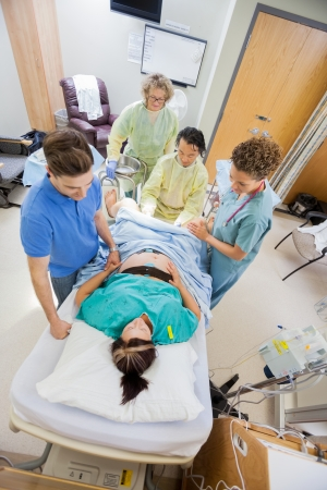 delivery room: High angle view of doctors with nurse operating pregnant woman during delivery in operating room