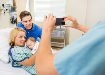 Closeup of female nurse photographing couple with newborn baby through mobilephone in hospital room photo