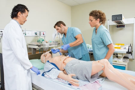 Male nurse adjusting endotracheal tube on dummy patient while colleague and doctor looking at it in hospital photo