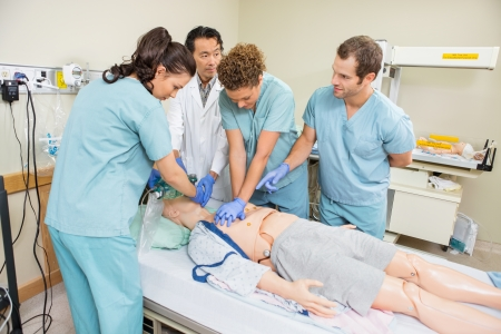 Doctor and nurses performing CRP on dummy patient in hospital room photo