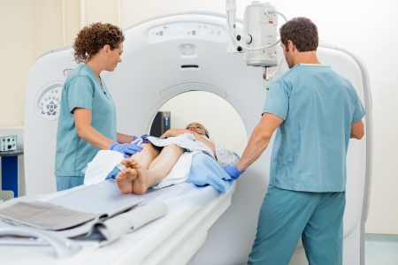 Nurses preparing female patient for CT scan in examination room photo