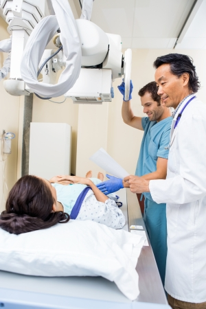 imaging: Doctor and nurse preparing young patient for xray in examination room