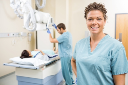 Portrait of radiologist smiling while colleague preparing patient for xray in examination room photo