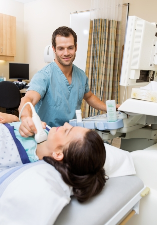 Young male nurse performing ultrasound on patients neck in hospital room photo