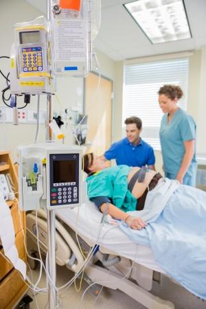 homme enceinte: IV et équipements péridurale avec l'infirmière et homme regardant la femme enceinte couchée sur le lit à l'hôpital Banque d'images