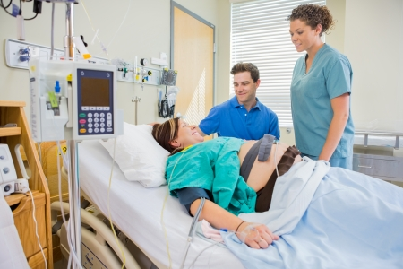 Happy nurse and man looking at pregnant woman lying on bed in hospital photo