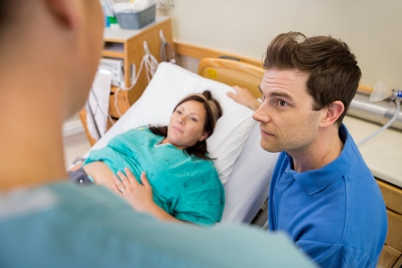 High angle view of mid adult man and pregnant woman listening to nurse in hospital room photo