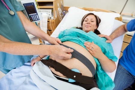 Midsection of nurse attaching fetal monitoring belts on pregnant woman's stomach in hospital room photo
