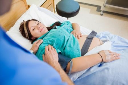 sala parto: Angolo alto ritratto di donna incinta sorridente mentre viene consolata dal marito in ospedale