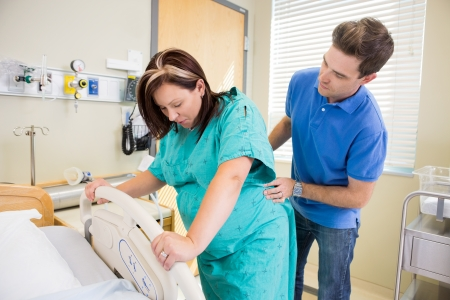 bl: Pregnant woman undergoing a contraction during labour with husband massaging lower back Stock Photo
