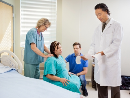 Male doctor examining ctg report with birthing mother, husband and nurse photo