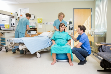 Nurse and man consoling pregnant woman sitting on fitness ball in hospital