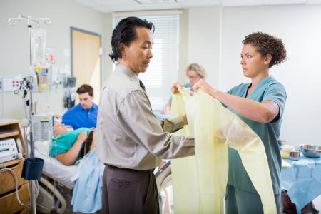 operation gown: Enfermera para ayudar a m�dico en el uso de traje de la operaci�n con la mujer embarazada y el hombre en el fondo
