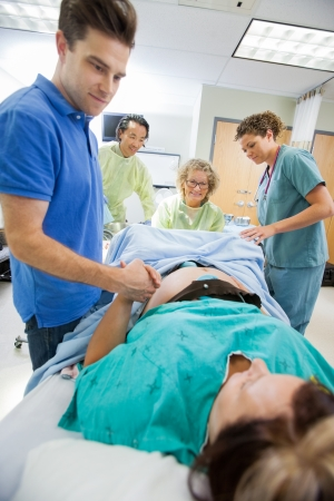 delivery room: Caring mid adult man holding womans hand during delivery in hospital room