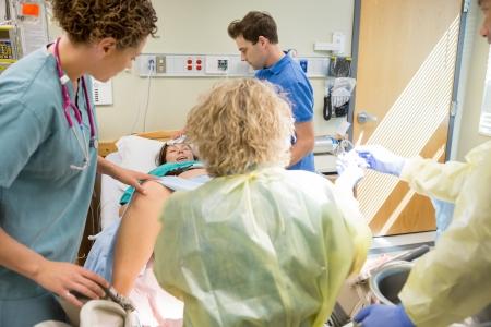 operation gown: Mujer que tiene dar contracci�n luz en el hospital con el equipo m�dico preparado.
