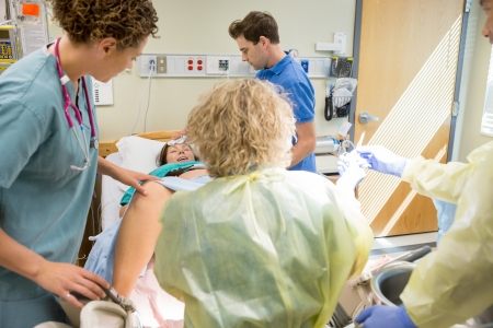 Woman having contraction giving birth in hospital with medical team ready.