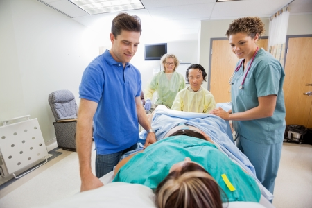 delivery room: Smiling medical team and husband looking at pregnant woman during delivery in operating room Stock Photo