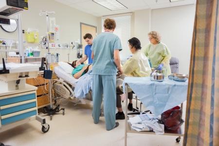 Medisch team actief zwangere vrouw terwijl man die zich door in het ziekenhuis kamer Stockfoto