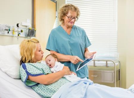 sala parto: Coppia infermiera femminile che spiega relazioni su tavoletta digitale alla donna con babygirl neonato in ospedale