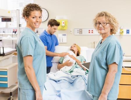sala parto: Ritratto di infermieri sorridente in piedi contro coppia con il neonato in ospedale