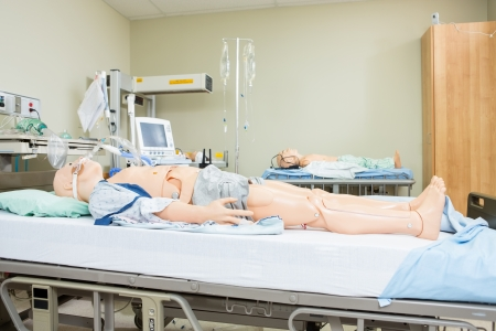 Medical dummies lying on hospital bed photo