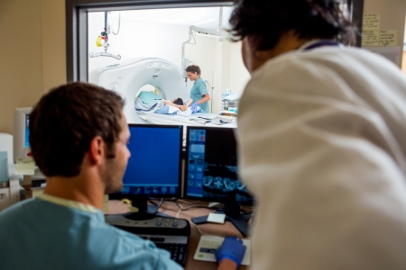 Radiologist and nurse operating computers while nurse preparing patient for CT scan in hospital photo