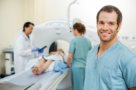 tomography: Happy male nurse with colleague and doctor preparing patient for CT scan in hospital