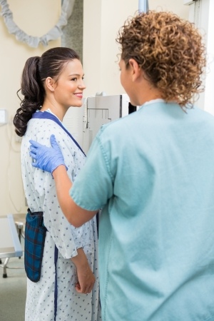 Female patient looking at nurse before getting chest xray in examination room photo