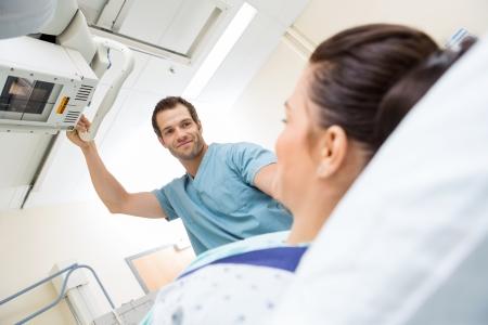 병실에서 환자에 대한 미 기계를 조정하는 남자 간호사의 낮은 각도보기