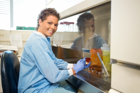 research facilities: Side view portrait happy female researcher with petridish working in laboratory