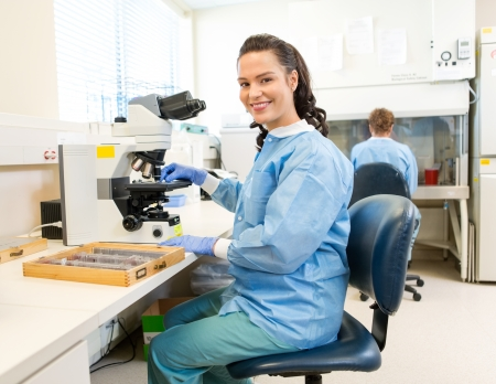 research facilities: Portrait of happy female researcher with microscope and samples tray working in laboratory