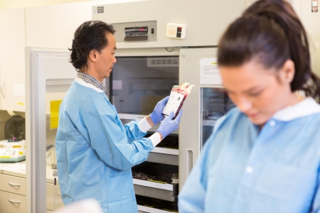 lab tech: Lab tech retreiving bag of red blood cells from blood bank in hospital Stock Photo