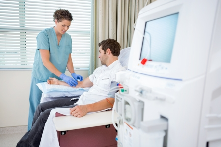 Mid adult female nurse injecting patient for renal dialysis treatment in hospital room Stock Photo