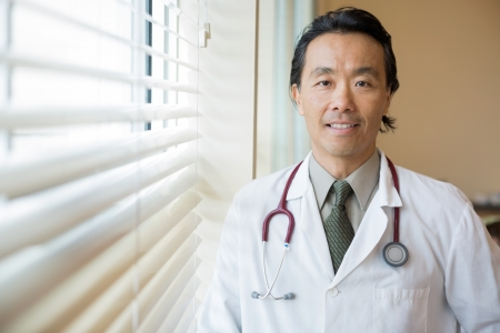 Portrait of Asian male doctor with stethoscope around neck standing in hospital room photo