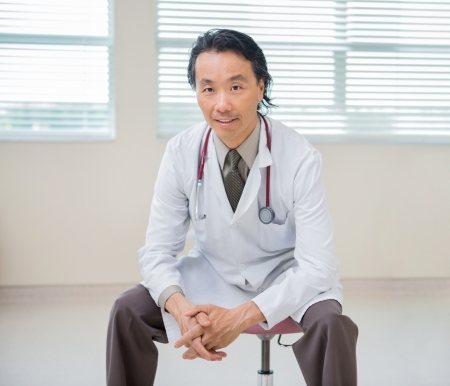 Portrait of Asian male doctor sitting on chair with patient in background at hospital room photo