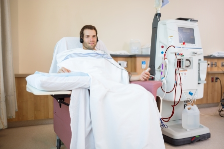 Portrait of young male patient listening to music while receiving renal dialysis treatment in hospital room