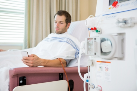 Young male patient using mobilephone waiting for renal dialysis
