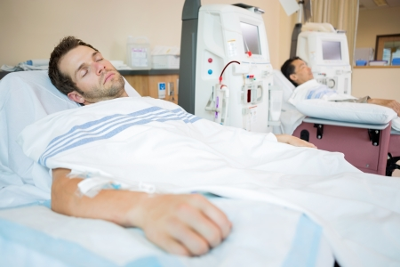 Male patients sleeping while receiving renal dialysis in chemo room at hospital