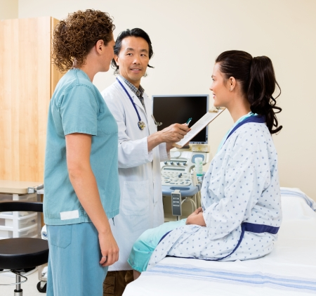health facilities: Mature doctor with nurse and patient in sonography room Stock Photo