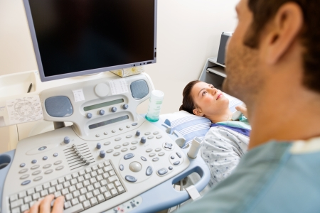 Male nurse performing ultrasound procedure in hospital room photo