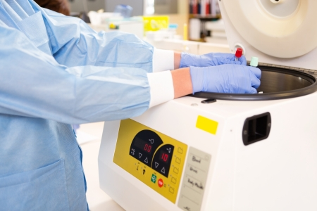centrifuge: Lab tech loading test tubes in centrifuge